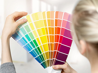 Women selecting colors from a color swatch book.