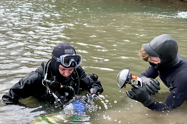 scuba diving to feed trout fish during video shoot